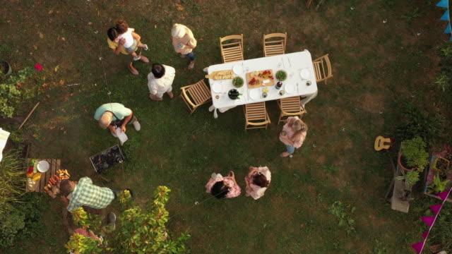 裏庭でのパーティーで楽しい時間を過ごしている古い友人 - 懇親会点の映像素材/bロール
