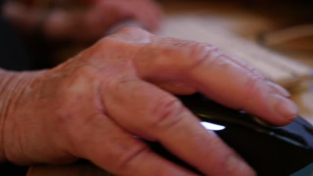 old hand uses computer mouse - ワーキングシニア点の映像素材/bロール