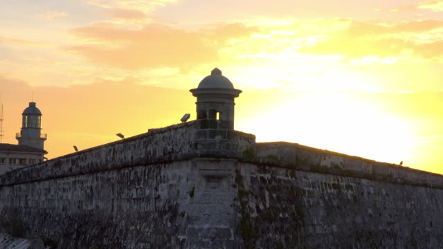 Old Havana, Cuba: Golden sunset at 'El Morro' which is a colonial architecture Spanish military fortress