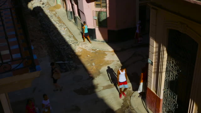 old havana cuba street scene with people crossing and bike taxi in day with dramatic light
