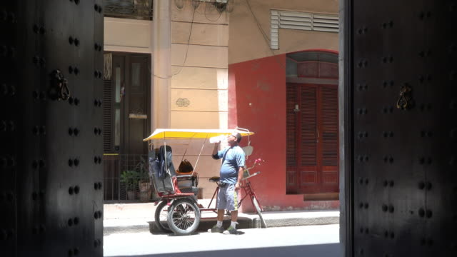 old havana, havana, cuba-july 1, 2014: the pedicab is parked by the sidewalk and its operator drinks water from a plastic bottle. the image is framed... - pedicab stock videos & royalty-free footage