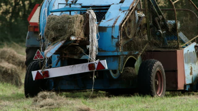 old hay baler making cubes of hay - hay baler stock videos & royalty-free footage