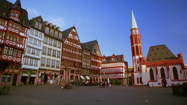 pan old houses (romer) + square (romerberg) with people / church in background (nikolaikirche) / frankfurt - städtischer platz stock-videos und b-roll-filmmaterial