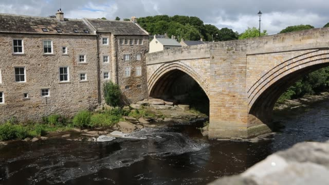 vídeos de stock, filmes e b-roll de old housing and the county bridge crossing the river tees in barnard castle, county durham, uk. - tees river