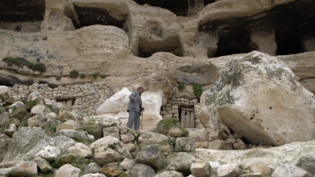 old kurdish man (cave dweller) in front of his cave home at the village of hasankeyf, southeast anatolia region, turkey - cliff dwelling stock videos & royalty-free footage