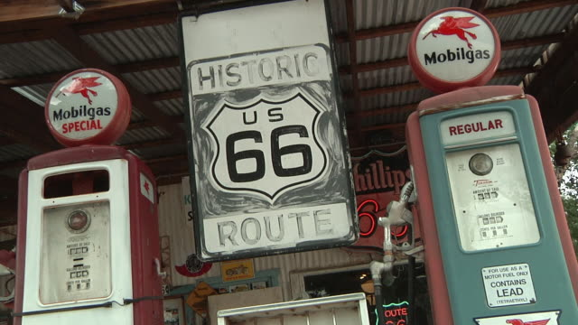 CU Old large historic route 66 sign swinging in breeze at an old dilapidated gas station / Flagstaff, Arizona, USA