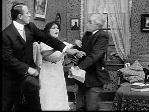 1915 b/w ms old man becoming angry at younger man after reading letter, tries to hit him woman calms him down - femmina con gruppo di maschi video stock e b–roll