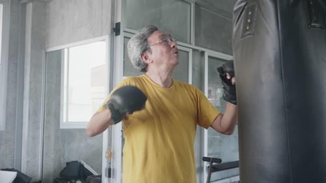 stockvideo's en b-roll-footage met oude man boksen in gym - assertiviteit