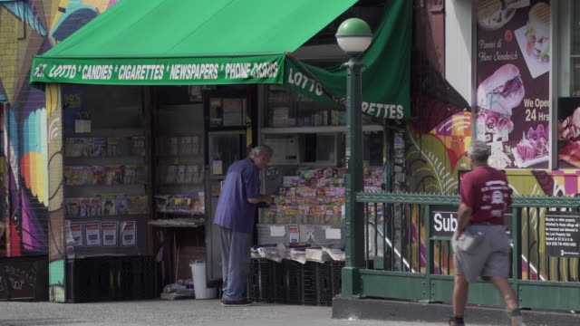 old man buys paper from newspaper stand outside subway station in brooklyn. - greenpoint brooklyn stock videos & royalty-free footage