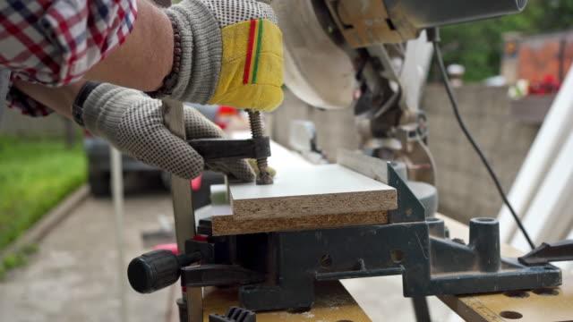 vídeos de stock, filmes e b-roll de velho apertando tábuas de madeira antes de cortá-las - serra circular