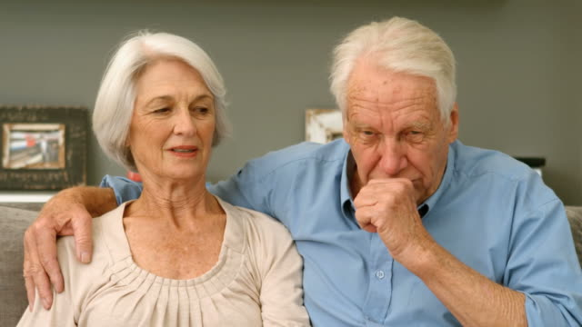 Old man coughing next to his wife