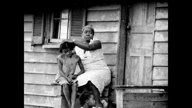 stockvideo's en b-roll-footage met old man / crowded streets and shoppers /african american people living in the city, woman and children sitting on front step / very overweight... - 1936