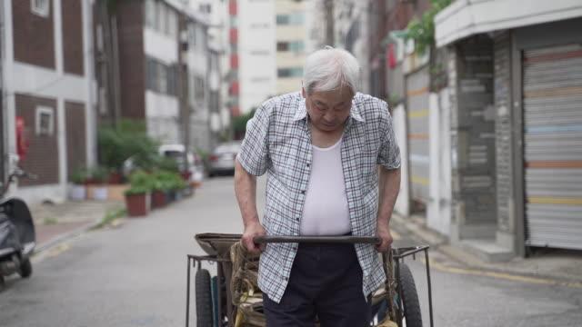 old man having hard time pulling handcart, seoul, south korea - ソウル点の映像素材/bロール