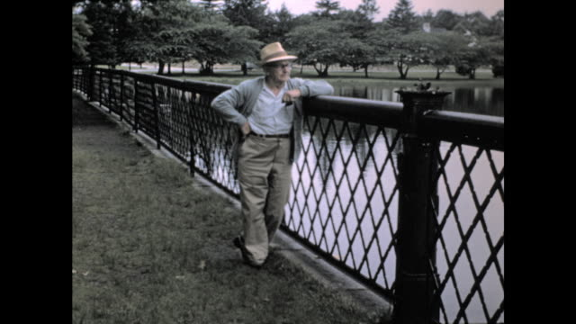 old man in glasses and sun hat posing standing next to a metal fence, looking out to the water; lake and trees in the background - lake stock videos & royalty-free footage