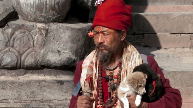 Old man in Nepal holding puppies and sitting on stone steps.