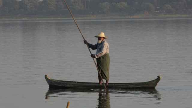 Old man in traditional clothing uses a stick to push boat NO
