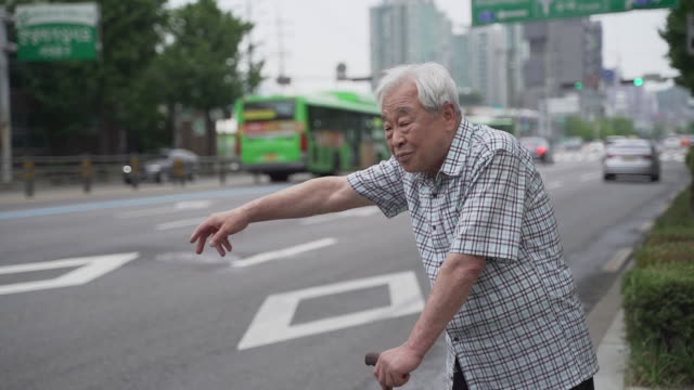 old man leaning on his walking stick and trying to hail a taxi, seoul, south korea - ソウル点の映像素材/bロール