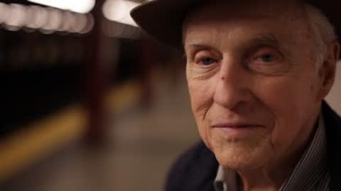vídeos y material grabado en eventos de stock de cu old man looking at camera with big smile   pedestrian walks in background on subway platform - viejo