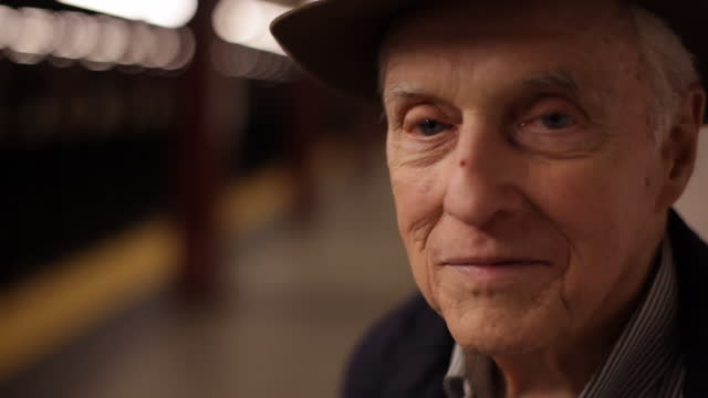 cu old man looking at camera with big smile   pedestrian walks in background on subway platform - schienenverkehr stock-videos und b-roll-filmmaterial