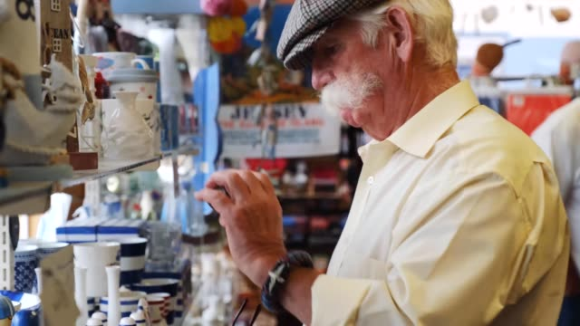 old man looking in gift shop - ギフトショップ点の映像素材/bロール