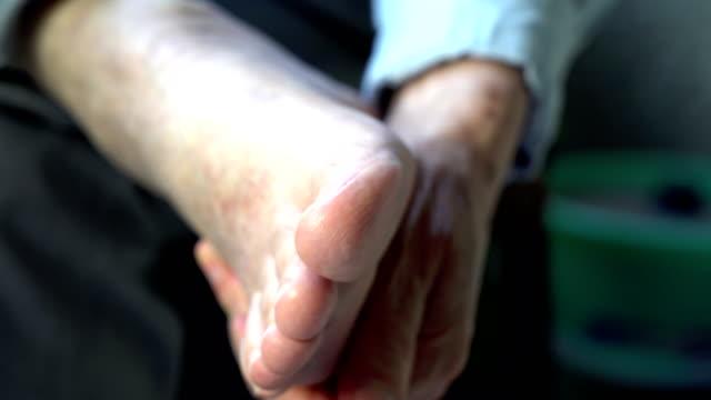 alter mann seine müden füße massieren - massieren stock-videos und b-roll-filmmaterial