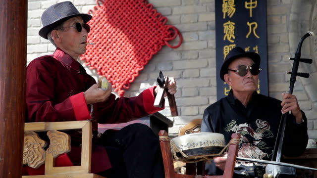 ls old man performing traditional opera in folk customs village during holidays in xingping, shaanxi, china - folk music stock videos and b-roll footage