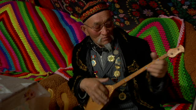 stockvideo's en b-roll-footage met old man playing two stringed instrument called topshur - alleen één seniore man