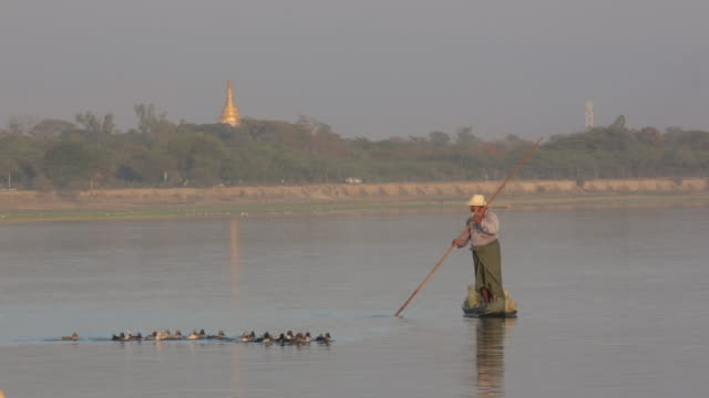 Old man pushing boat with temple in background
