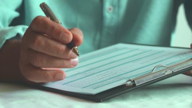 vídeos de stock, filmes e b-roll de formulário de leitura do homem idoso - formulário de aplicação