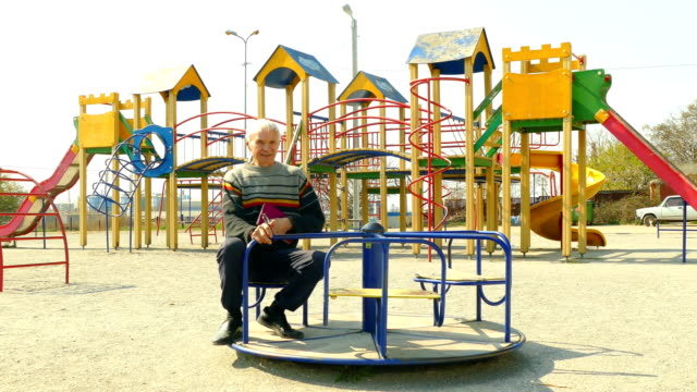 old man rides on a children's carousel in an empty playground - roundabout stock videos & royalty-free footage