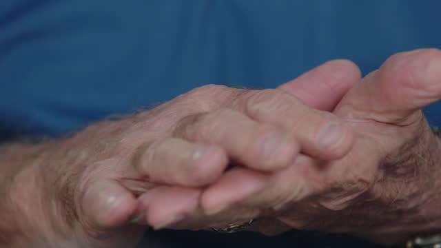 ECU SLO MO. Old man rubs hands together in slow motion.