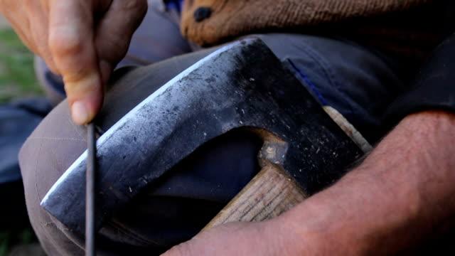 vídeos de stock, filmes e b-roll de afiação machado velho - afiado
