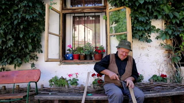 vídeos de stock e filmes b-roll de old man sharpening axe - documentário