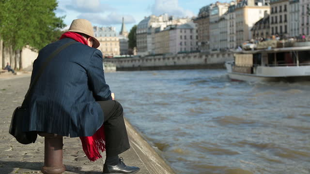 old man sits and reads by the seine as tour boat passes. - francia video stock e b–roll