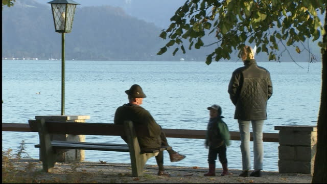 vidéos et rushes de old man sits on bench overlooking mondsee lake with woman and child milling about - banc public
