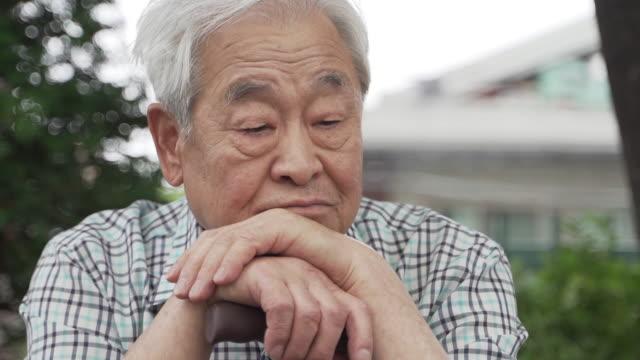 vídeos de stock, filmes e b-roll de old man spending time alone resting his head on a walking stick, seoul, south korea - boca humana