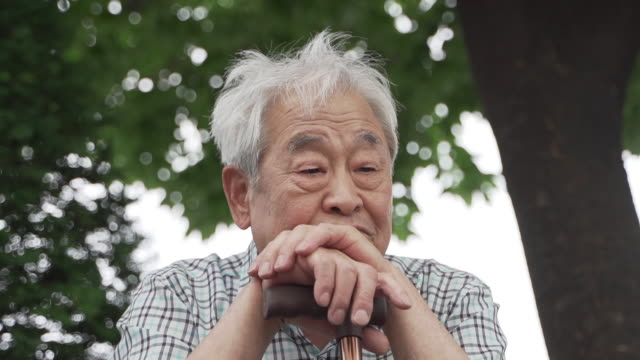 vidéos et rushes de old man spending time alone resting his head on a walking stick, seoul, south korea - nez humain