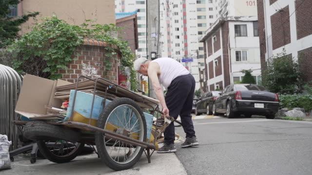 old man stacking wastepaper on his handcart and pulling it, seoul, south korea - ソウル点の映像素材/bロール