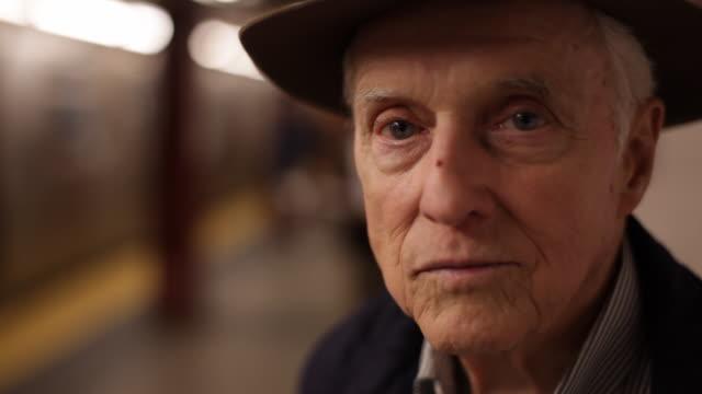 Old man stares at camera on subway platform as train arrives