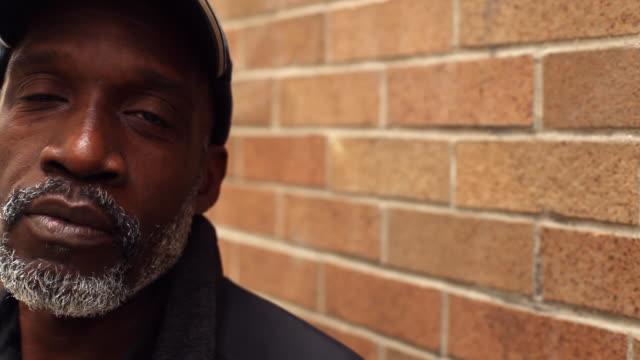 vidéos et rushes de old man stares into camera as door closes behind him on new york city street corner - afro américain