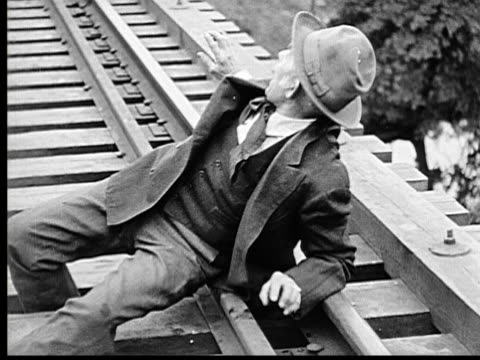 stockvideo's en b-roll-footage met 1915 b/w ms old man stuck on tracks because of twisted ankle, distressed because train is coming - 1915
