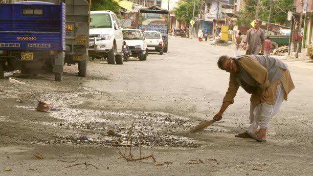 old man sweeping in streets of india - dhoti video stock e b–roll