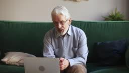 Old man talking making skype video call looking at laptop