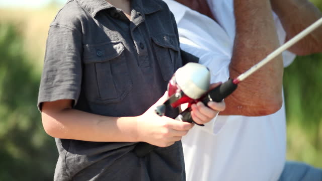 vídeos de stock e filmes b-roll de ms old man teaching  little boy how to fishing / tracy, ca, united states - membro do elenco