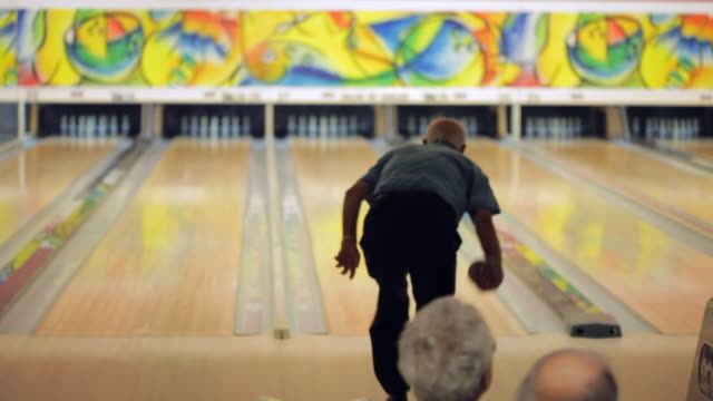 Old man throws ball on duckpin bowling pins for strike