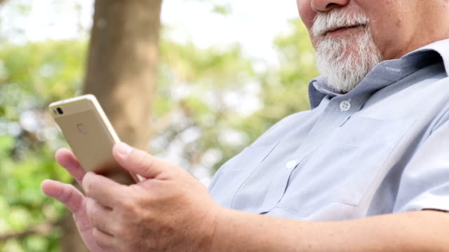 Old man using a smartphone outdoors