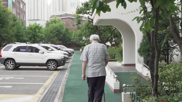 old man walking alone in the apartment complex, seen from behind, seoul, south korea - loneliness点の映像素材/bロール