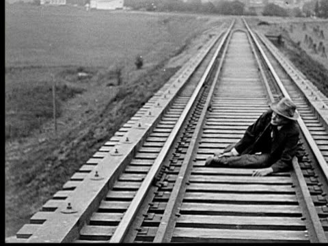 1915 B/W WS Old man walking on railroad tracks twists ankle and falls onto tracks, crawls forward