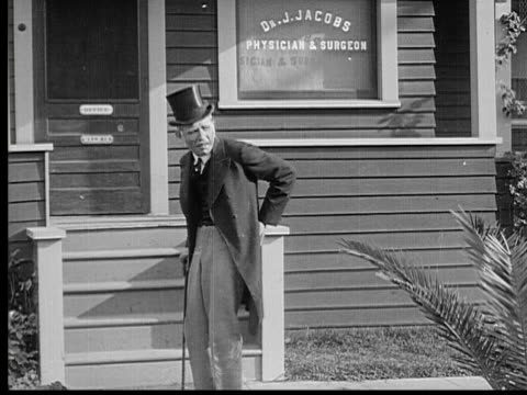 1913 B/W WS Old man walking up to doctor's office holding his back and walking with cane / USA