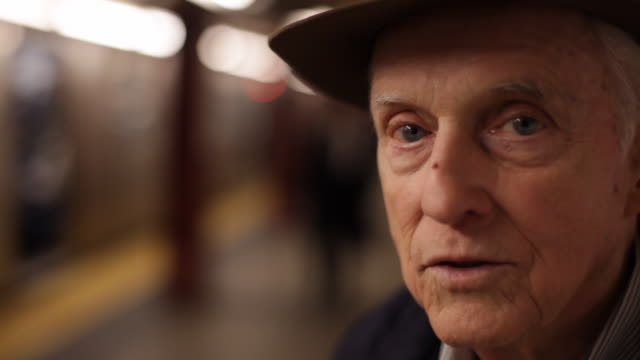 Old man watches strangers and trains pass on subway platform, stares into camera